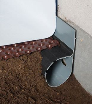 Closeup of a crawl space drainage system installed in